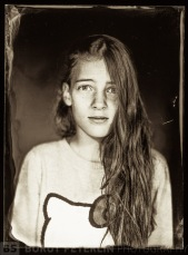 A portrait of my oldest daughter on wet plate collodion negative, illuminated by mighty flash burst. That's why the expression.