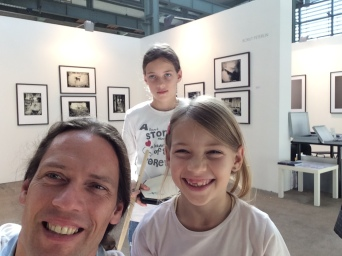 With my daughters at ArtMarket Budapest with my photographs in the back.